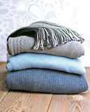 Pile of warm wool clothing on a wooden table Royalty Free Stock Photography