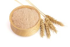 Pile of wheat bran in wooden bowl with ears isolated on white background