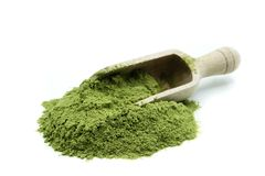 Pile of wheatgrass powder with wooden scoop on white background royalty free stock photography