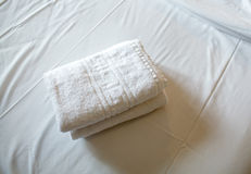 Pile of white clean towels on the bed Royalty Free Stock Photos