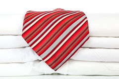 Pile of white dress shirts with red tie. Royalty Free Stock Photo