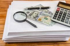 Pile of white paper, dollars, calculator, magnifier and pen royalty free stock photo
