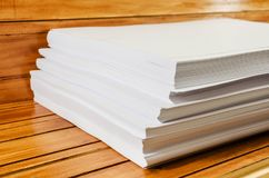 Pile of white paper on a wooden table stock image