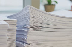 Pile of white papers sheet near window stock images