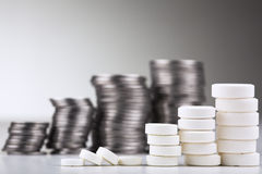 Pile of white pills. (in the form of a staircase) against pile of coins Stock Photography