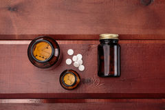 Pile of white pills and glass bottles for medicines.Top view Royalty Free Stock Image