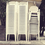 Pile of white plastic chairs Stock Images