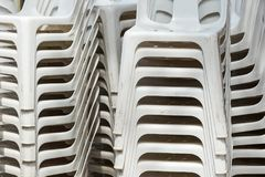 Pile of white plastic deck chairs. stock photo