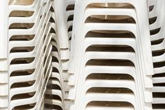 Pile of white plastic deck chairs. Pile of white plastic deck chairs, abstract texture or background. Toned stock photo