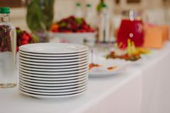 Pile of white plates on catering buffet. Pile of white plates on catering buffet Stock Image