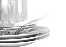 Pile of white plates, glasses, forks, spoons. Royalty Free Stock Images