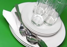Pile of white plates, glasses, forks, spoons. Royalty Free Stock Photos