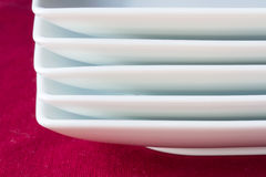 Pile of white plates on red Stock Images