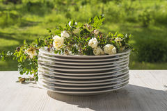 Pile of white plates and wild roses Royalty Free Stock Image