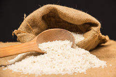 A pile of white rice sitting on a brown burlap Royalty Free Stock Photography