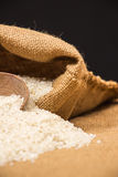 A pile of white rice sitting on a brown burlap Stock Image