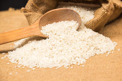 A pile of white rice sitting on a brown burlap Stock Photography