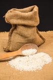 A pile of white rice sitting on a brown burlap Royalty Free Stock Image