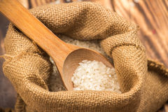 A pile of white rice sitting on a brown burlap Royalty Free Stock Photos