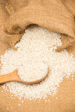 A pile of white rice sitting on a brown burlap Royalty Free Stock Photo