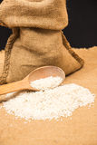 A pile of white rice sitting on a brown burlap Stock Images