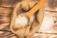A pile of white rice sitting on a brown burlap Stock Photo