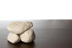 Pile of white rocks on dark brown wood shelf Royalty Free Stock Photo