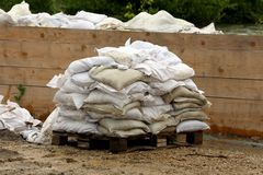 Pile of white sandbags used for flood protection put on wooden pallet waiting to be removed after flood surrounded with muddy. Water and wooden boards holding stock photo