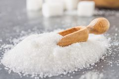 A pile of white sugar sand with a wooden scoop on a dark background. A pile of white sugar sand with a wooden scoop on a dark background Stock Image