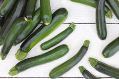 Pile of whole courgettes from above on white weathered wood. Royalty Free Stock Photos