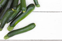Pile of whole courgettes from above on white weathered wood. Stock Images