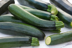 Pile of whole courgettes on white weathered wood. Stock Photos