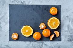 Pile of whole and half cut fresh tangerine and orange on cutting board, close-up. Pile of whole and half cut fresh tangerine and orange on black stone cutting stock photo