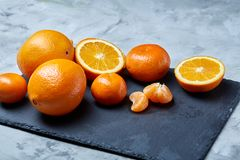 Pile of whole and half cut fresh tangerine and orange on cutting board, close-up. Pile of whole and half cut fresh tangerine and orange on black stone cutting stock photos
