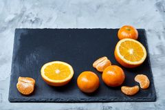Pile of whole and half cut fresh tangerine and orange on cutting board, close-up. Pile of whole and half cut fresh tangerine and orange on black stone cutting royalty free stock images