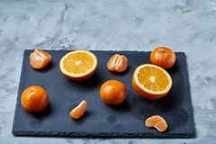 Pile of whole and half cut fresh tangerine and orange on cutting board, close-up. Pile of whole and half cut fresh tangerine and orange on black stone cutting stock image