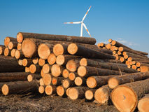 Pile wood logs with a wind turbine Royalty Free Stock Photos