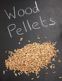 Pile of wood pellets on  a blackboard with the words wood pellet Stock Photo