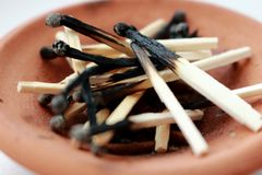 Pile of wooden burnt matches in brown clay plate. Matches close up. Royalty Free Stock Photography