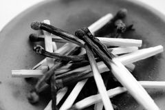 Pile of wooden burnt matches in clay plate black and white. Matches close up. Royalty Free Stock Photo