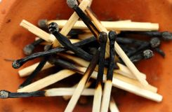 Pile of wooden burnt matches in brown clay plate. Matches close up. Stock Photos