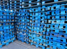Pile of wooden euro pallets painted in blue. Wooden euro pallets painted in blue stacked on the ramp of a transport company Stock Photos