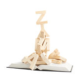 Pile of wooden letters over the book. Pile of wooden letters over the opened book's surface, composition isolated over the white background Stock Image