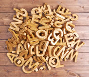 Pile of wooden letters over the wooden surface. As a typography background composition Royalty Free Stock Images