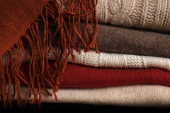 Pile of Woolen Sweaters and a Scarf. Several woolen sweaters stacked on top of each other and a scarf on top of them royalty free stock photo