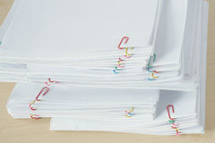 Pile of workload paperwork and reports with colorful paper clip Stock Photo