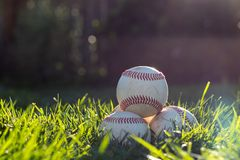 Old, worn baseballs stacked in the grass in the warm, afternoon sun