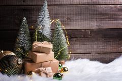 Pile of wrapped presents, decorative fir trees, golden and green balls and fairy lights stock images