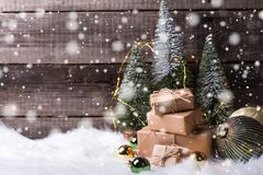 Pile of wrapped presents, decorative fir trees, golden and green balls and fairy lights stock image