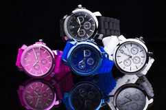 Pile Of Wrist Watches. Colorful Pile Of Wrist Watches On Black Background With Reflection stock photos